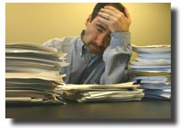 man at desk with piles of documents